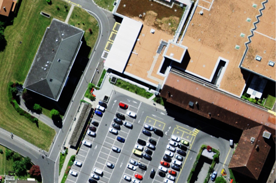 Aerial image showing a hospital with its accesses and parking spaces.